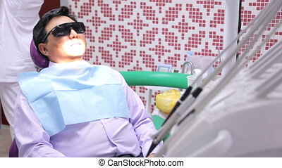 Asian male sitting in dental chair with glasses from...