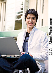 Asian male student and laptop