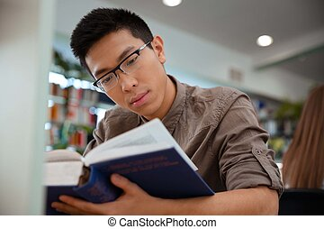 Asian male student reading book in university - Portrait of...