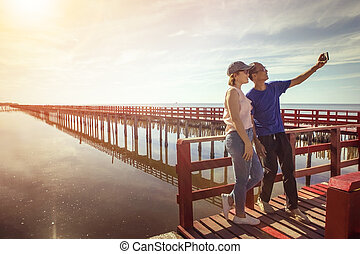 asian man and woman taking a photo on red wood bridge against sun rising sky