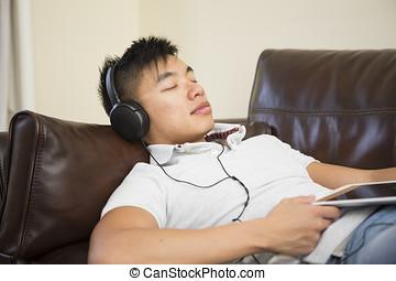 Asian man asleep on sofa holding a digital tablet.