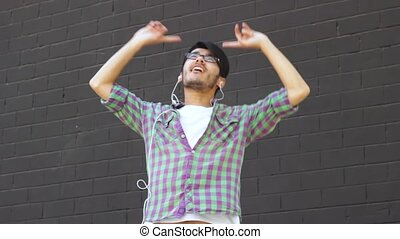 Asian man dancing against gray wall - Happy asian young man...