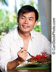 Asian Man Dining - An attractive asian man eating at a...