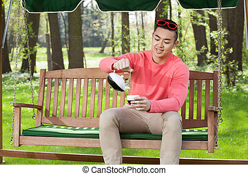 Asian man drinking tea in garden