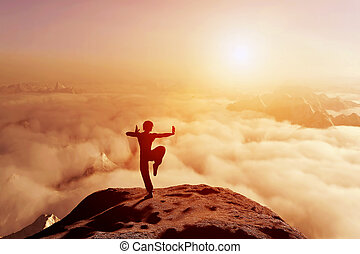 Asian man, fighter practices martial arts in high mountains above clouds at sunset. Kung fu and karate pose. Also concepts of discipline, concentration, meditaion etc