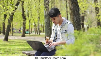 Asian man freelancer working on laptop and eating ice-cream