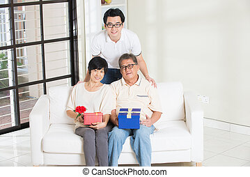 asian man giving present to father and mother
