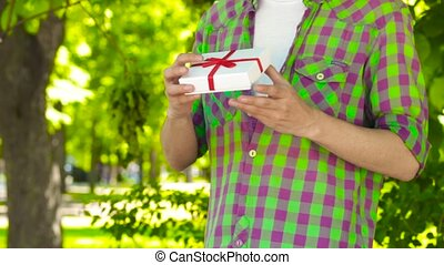 Asian man got and opening gift in park - Handsome Asian guy...
