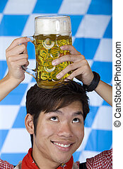 Asian man having Oktoberfest beer stein on his head and smiles