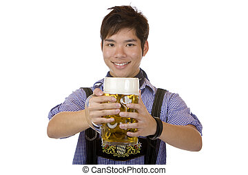 Asian man holding an Oktoberfest beer stein into camera and smiles happy. Isolated on white.