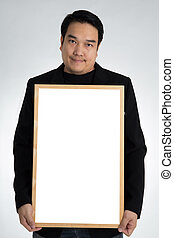 Asian man in black suit holds an empty white board