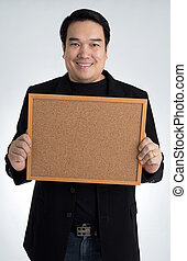 Asian man in black suit holds an empty woodboard