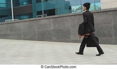 Asian man in black suit walking on the street