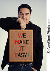 Asian man in black suit with WE MAKE IT EASY! message on white board