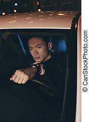 Asian man in car at night.