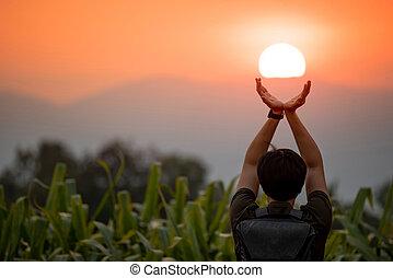 Asian man in corn field holding the sun