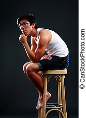 Asian man in glasses sitting on the chair over black background