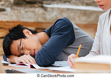 Asian man in glasses sleeping on the lesson