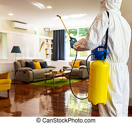 Close up medical staff in personal protective equipment PPE suit with coronavirus COVID-19 disinfectant spray with  living room background. Delivery health care hygiene and disinfection concept