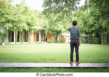 Asian man is holding the leaf and branch of big tree in relaxing feeling on wood walkway step with blur garden behind.