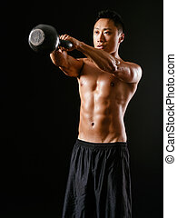 Photo of an Asian male exercising with a kettle bell over dark background.