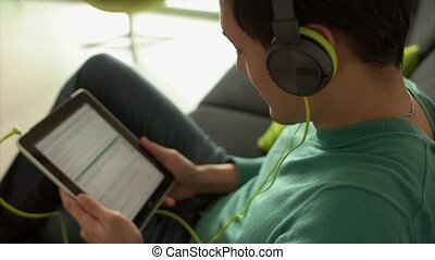 Asian Man Listening Music Podcast On Tablet PC With Earphones