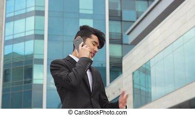 Asian man making business calls