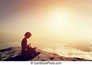 Asian man meditates in yoga position in high mountains above clouds at sunset