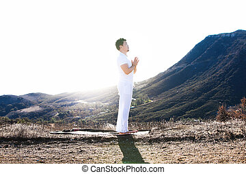 Asian man meditates in yoga position on high mountains above blue sky.