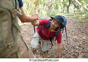 man need help to get up while hiking
