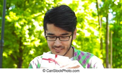 Asian man opening gift in park - Handsome Asian guy smiling...