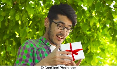 Asian man opening gift in park in summer - Handsome Asian...