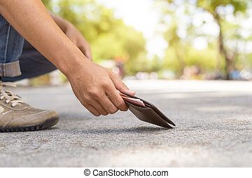 Asian man picking black wallet on the road in tourist...