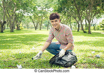 Asian man picking up plastic household waste in park