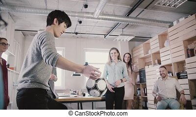 Asian man plays with football in office during break. Happy...