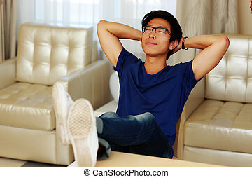 Asian man relaxing at home