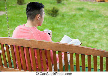 Asian man relaxing in a garden