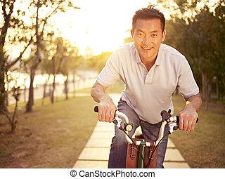 asian man riding bike outdoors at sunset