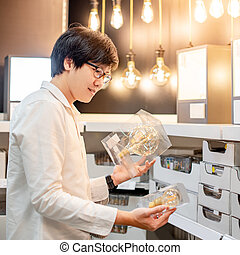 Asian man shopping electrical light bulb - Asian man shopper...