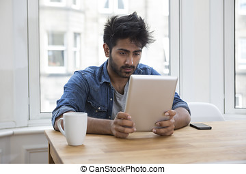 Asian man sitting at a table reading a Tablet PC.