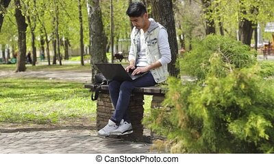 Asian man sitting in the park and working on laptop