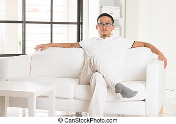 asian man sitting on sofa