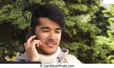 Asian man talking by phone sitting in the park
