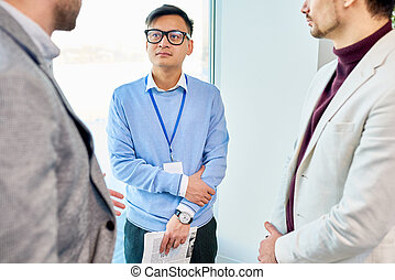 Asian Man Talking to Business People