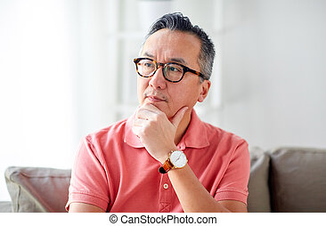 asian man thinking at home - people concept - asian man...
