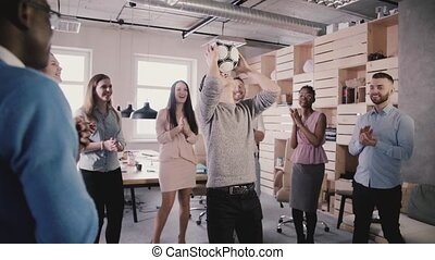 Asian man tries to hold football on head in office. Happy...