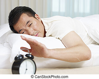 asian man trying to stop alarm clock