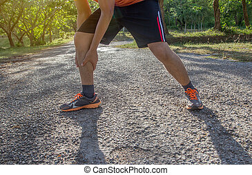 Asian man use hands hold on his ankle while running on road in the park.