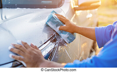 Asian man using blue sponge with soap to washing the car at outdoor in sunset time