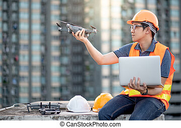 Young Asian man working with drone laptop and smartphone at construction site. Using unmanned aerial vehicle (UAV) for land and building site survey in civil engineering project.